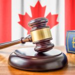 A Gavel And A Law Book in front of Canadian flag