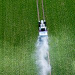 Three Tractors Spray Pesticides On A Green Field Top View